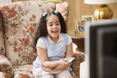 Young girl watching television — Stockfoto