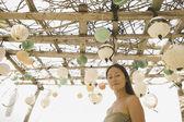 Woman standing beneath awning on beach — Stock Photo