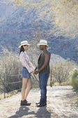 Young couple in cowboy outfit standing on dirt path — Stock Photo