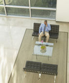 Businessman talking on a cell phone in lobby area — Stock Photo