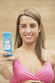 Young woman holding a mobile phone — Stok fotoğraf