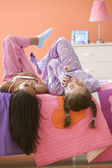 Two girls laying on bed talking on cell phone — Stock Photo