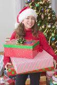 Portrait of girl in Santa hat in front of Christmas tree holding gifts — Stock Photo
