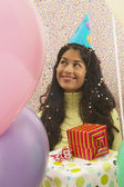 Young woman smiling at birthday party — Stock Photo