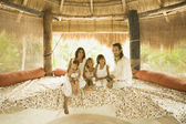 Family sitting on bed in hut — Stock Photo
