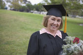Older graduate holding flower bouquet — Stock Photo