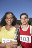 Two male track athletes holding trophy — Stock Photo