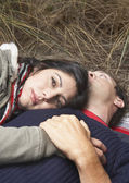 Portrait of couple laying down in beach grass — Stock Photo