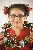 Young girl holding a wreath of jingle bells around her neck — Stock Photo