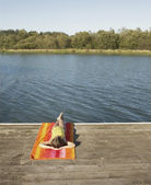 Young girl relaxing by a lake — Stock Photo