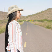 Woman standing in road wearing cowboy hat — Stock Photo