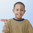 African American boy holding grilled hot dog on fork - Stock Photo