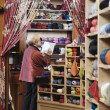 Woman taking inventory in yarn shop - Zdjcie stockowe