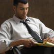 Businessman sitting and writing notes — Stock Photo
