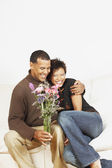 Couple holding a vase of flowers — Stock Photo