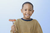 African American boy holding grilled hot dog on fork — Stock Photo