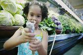 Retrato de menina com pulverizador na mercearia — Foto Stock