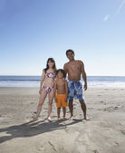 Portrait of family in bathing suits at beach — Stock Photo