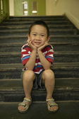 Young boy smiling on staircase — Stock Photo