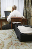 Businessman with laptop at desk in hotel — Stock Photo