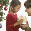 Father giving daughter Christmas gift - Stock Photo