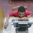 High angle view of a young boy operating a computer at the library — Stock Photo