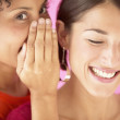 Woman whispering in friend's ear — Stockfoto