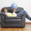 Side view of woman holding globe in armchair - Stock Photo