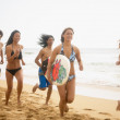 Group of young adults running on beach with surfboards — Stock Photo