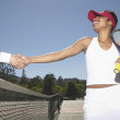 Players shaking hands on tennis court — Stock Photo