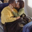 Mature couple cuddling on airplane - Stock Photo