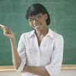 Portrait of female teacher in classroom - Stockfoto