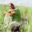 Young man sitting in sea grass on beach — Stock Photo