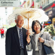 Senior couple with sun umbrella on urban street — Stock Photo