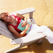 Stock Photo: High angle view of a young woman sitting on a beach chair