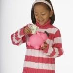 Girl putting money in piggy bank — Stock Photo