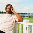 Young man using cell phone on at waterfront - Stock Photo