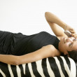 Woman talking on cell phone while laying on zebra hide — Stock Photo