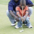 Father and son on golf course - Stock Photo