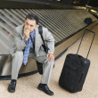 Businessman waiting for luggage — Stock Photo