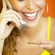 Woman talking on cell phone while holding credit card - Stock Photo