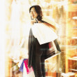 Young woman standing holding shopping bags — ストック写真
