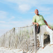 Young man leaning on beach fence — Stock Photo