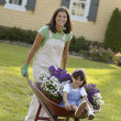 Portrait of mother and daughter with wheelbarrow — Stock Photo