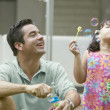 Father and daughter blowing bubbles — Stock Photo