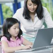 Teacher helping girl on laptop — Stockfoto