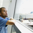 Man looking through airport window — Stock Photo
