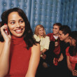Young woman taking phone call in night club - Stock Photo