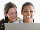 Young women laughing together at computer — Stock Photo