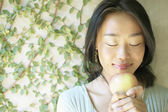 Woman with eyes closed holding apple outdoors — Stock Photo